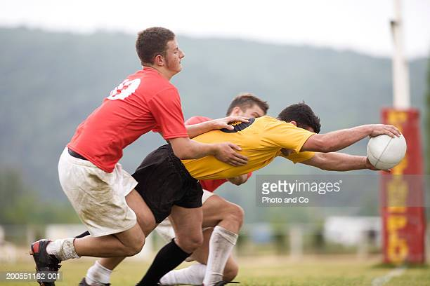 Young men playing rugby, players tackling opponent