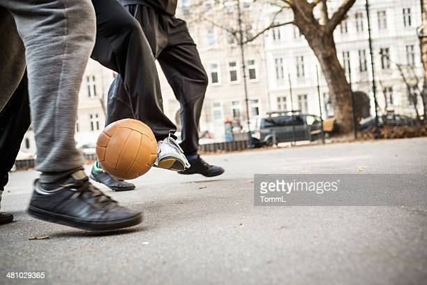 Young men playing soccer with vintage soccer ball
