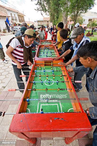 CONTENT] Young men playing table football on the village plaza of Tarabuco fussball foosball babyfoot outdoor recreation teams social game table...
