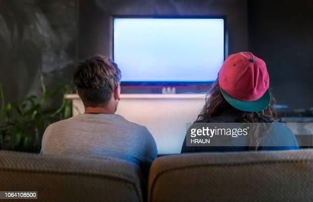 giovani che giocano ai videogiochi in televisione a casa - guardare con attenzione foto e immagini stock