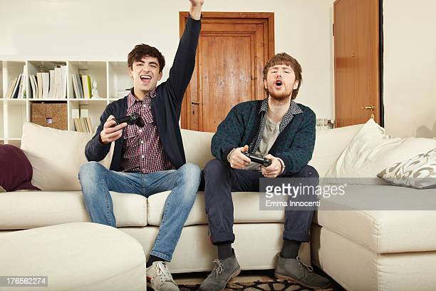 Young men playing video games on sofa