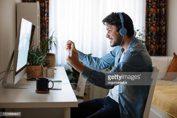 young men playing video games with desktop - stream stock pictures, royalty-free photos & images