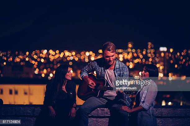 Young men plays guitar for his two friends on rooftop