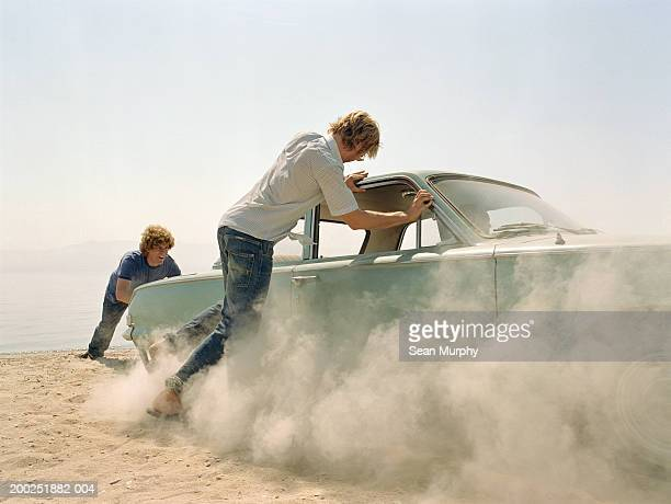 Young men pushing car stuck in sand