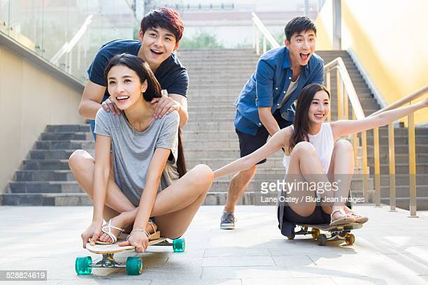 Young men pushing girlfriends on skateboards
