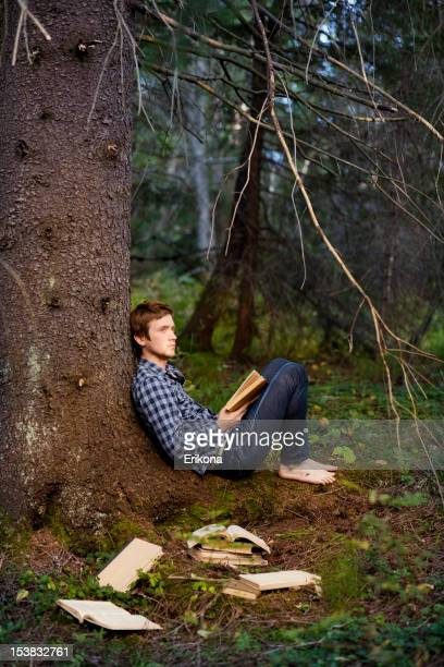 Young Men Reading Book in Dark Forest
