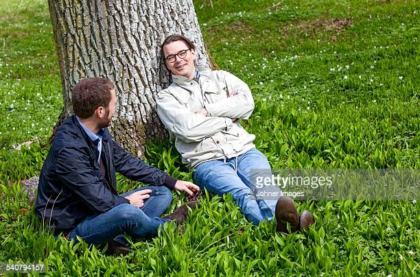 Young men resting under tree