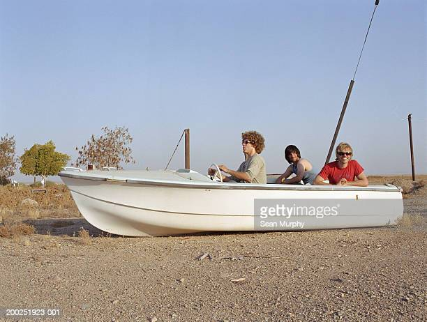 young men riding in boat docked on land - irony stock pictures, royalty-free photos & images