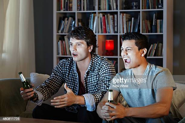 Young men shouting at tv, holding beer bottles
