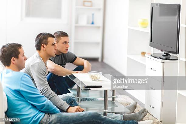 Young men sitting at home and watching TV.
