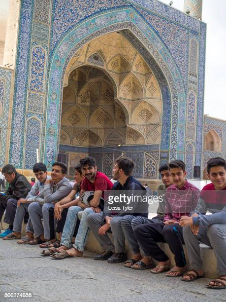 Young men sitting in the courtyard of the Masjede Jame in Esfahan the oldest Friday mosque in Iran The mosque is a good example of the evolution of...