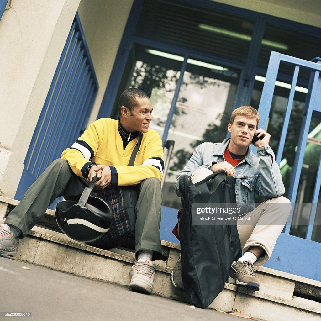 Young men sitting on steps with backpacks, one on cell phone. : Stockfoto