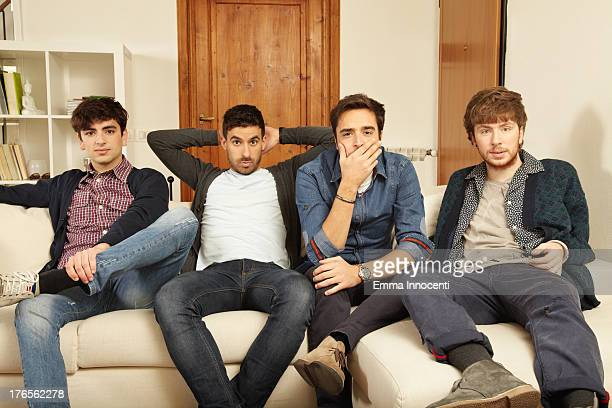 Young men sitting on the sofa looking puzzled