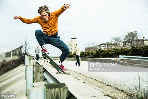 Young men skateboarding in urban environment.