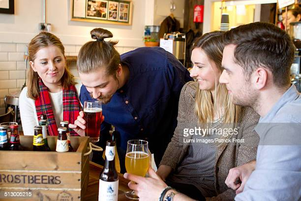 Young men smelling and tasting beer in pub, Dorset, Bournemouth, England