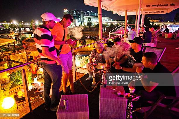 Young men smoking shisha as they spend the evening in the beach bar Bundespressestrand on August 20 2011 in Berlin Germany Berlin which is among...