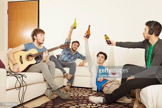 young men, sofa, celebrating, playing, guitar