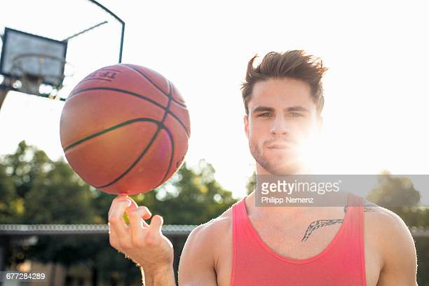 young men spinning basketball on finger