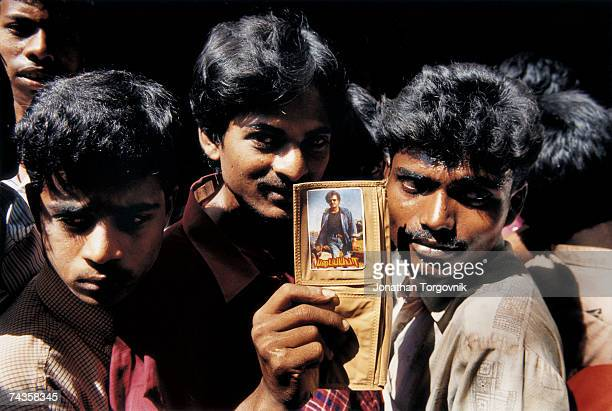 Young men standing in line waiting to enter Roopam Cinema January 1997 in Chennai India One of them displays a photo of film megastar Rajnikanth that...