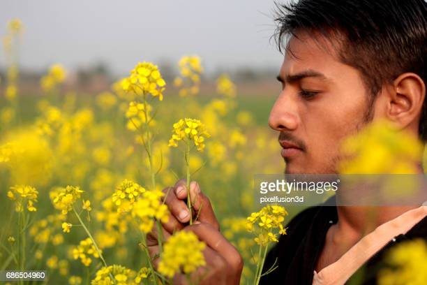 Young men standing in the field of mustard crop