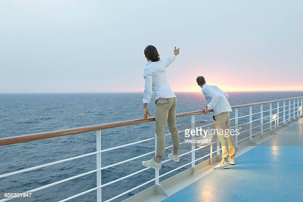 young men standing on deck of ship, watching sunset - passagier wasserfahrzeug stock-fotos und bilder