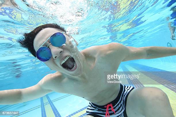 Young men swim under water