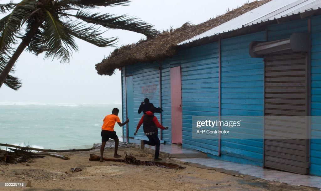 Young men take cover as winds lash the coastal city of Punta Cana, in the Dominican Republic, the eastermost tip of the La Espanola island it shares with Haiti, as Hurricane Maria approaches on September 20, 2017. Hurricane Maria slammed into Puerto Rico on Wednesday, cutting power on most of the US territory as terrified residents hunkered down in the face of the island's worst storm in living memory. The US and British Virgin Islands -- still struggling to recover from the devastation of Irma -- are also on alert, along with the Turks and Caicos Islands and parts of the Dominican Republic. / AFP PHOTO / Erika SANTELICES