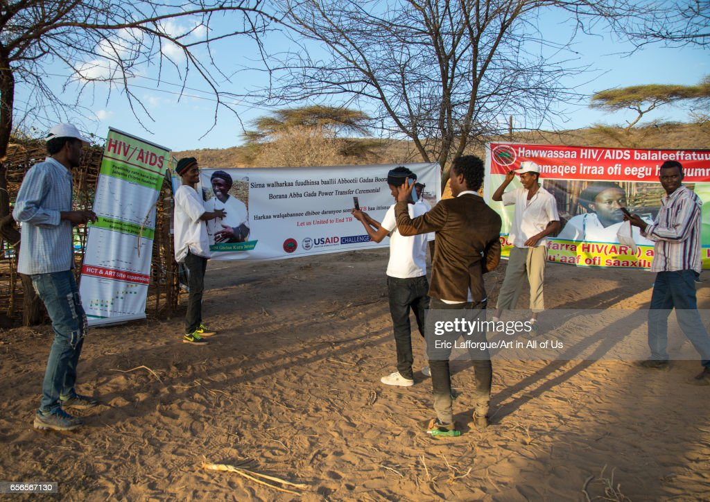 Young men taking pictures in front of HIV billboards during the Gada system ceremony in Borana tribe, Oromia, Yabelo, Ethiopia... : Nachrichtenfoto