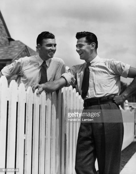 young men talking with each other near fence - 1930 1939 photos et images de collection