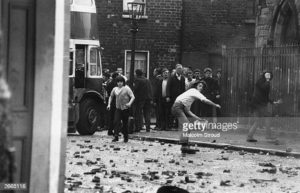 Young men throwing stones at the Royal Ulster Constabulary in the Falls Road area of Belfast Five Catholics were killed 60 injured and hundreds of...