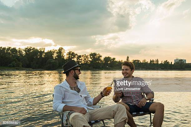 Young men toasting with beer bottles by lake