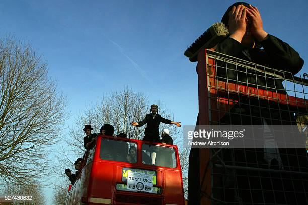 Young men tour the streets wearing fancy dress in an open top bus drinking and dancing while going round visiting local wealthy men collecting for...