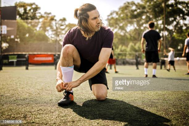 young men tying shoelace on soccer field - soccer competition stock pictures, royalty-free photos & images