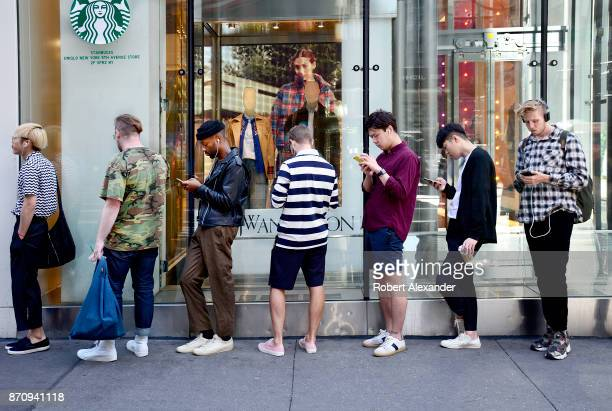 Young men use their smartphones as the wait in line for a Uniqlo clothing store to open on Fifth Avenue in New York New York