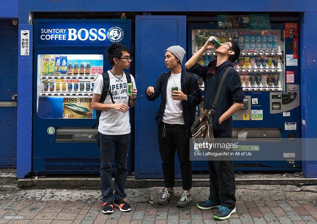Young men using a drinks vending machine, Kanto region, Tokyo, Japan... : News Photo