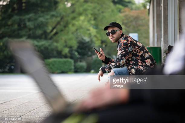 young men using laptops and mobile phones in public - kiosk stock pictures, royalty-free photos & images