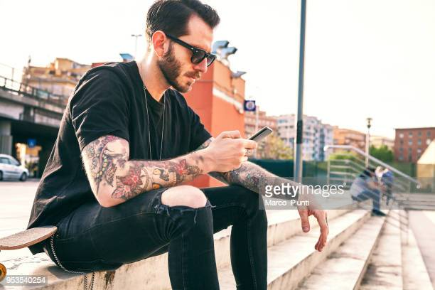 young men using smartphone - tattoo stock pictures, royalty-free photos & images