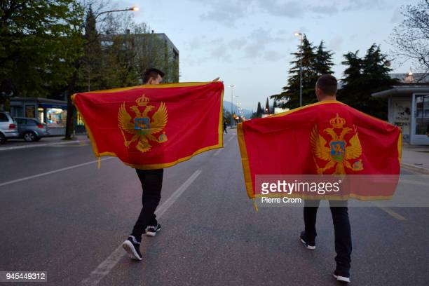 Young men walk on a street with Montenegrin flags on April 12 2018 in Podgorica Montenegro Citizens from Montenegro the youngest NATO member will...