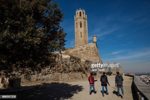 Young men walk past the Seu Vella on October 24 2017 in Lleida Spain Catalonia is one of 17 autonomous communities within Spain which were created as...
