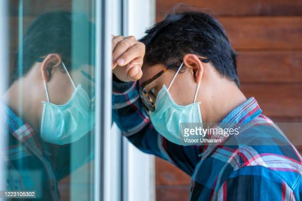 young men wearing protective mask to protect against covid-19 worried about unemployment. - uncertainty stock pictures, royalty-free photos & images