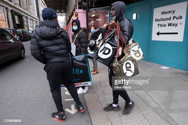 Young men who have been out shopping at JD Sports and are laden with many shopping bags as the national lockdown ends and the new three tier system...