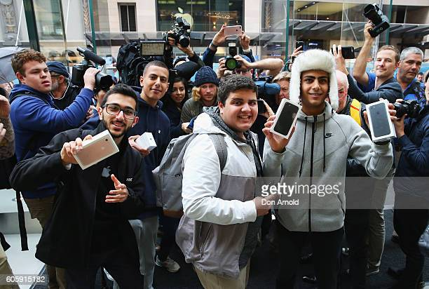 Young men who were the first to purchase the iPhone 7 pose with their phones at the Apple Store on September 16 2016 in Sydney Australia Apple's...