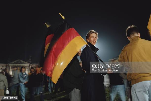 Young men with German flags during celebrations of the Fall of the Berlin Wall, November 1989. The border was opened on the evening of 9th November...