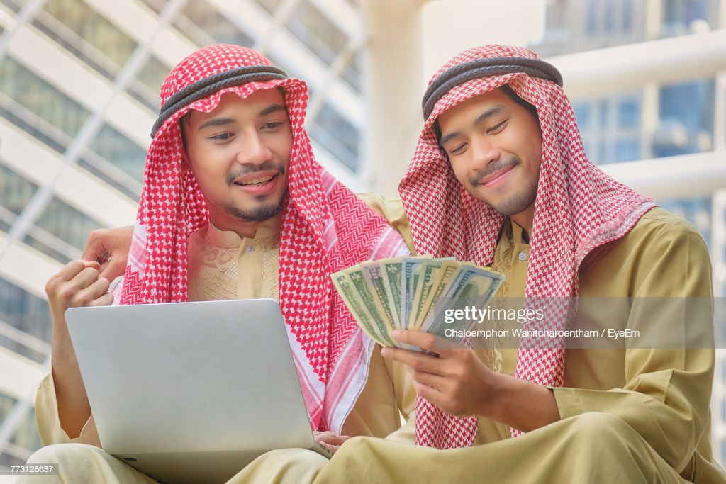 Young Men With Paper Currency And Laptop : Stock Photo