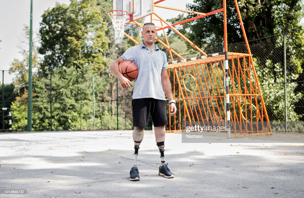 Young men with prosthetic legs on basketball court : Stock Photo