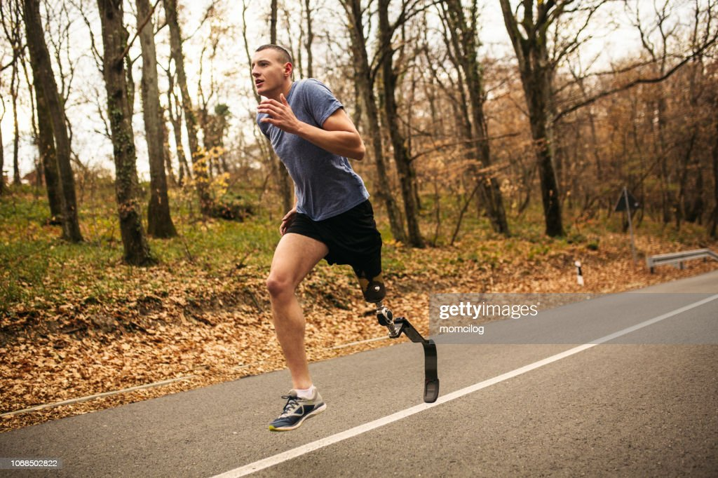 Young men with prosthetic legs running in the forrest : Stock Photo
