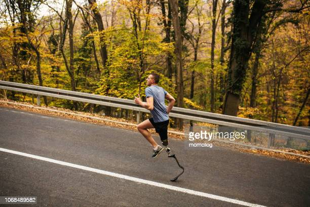 young men with prosthetic legs running uphill in the forrest - paraplegic stock photos and pictures