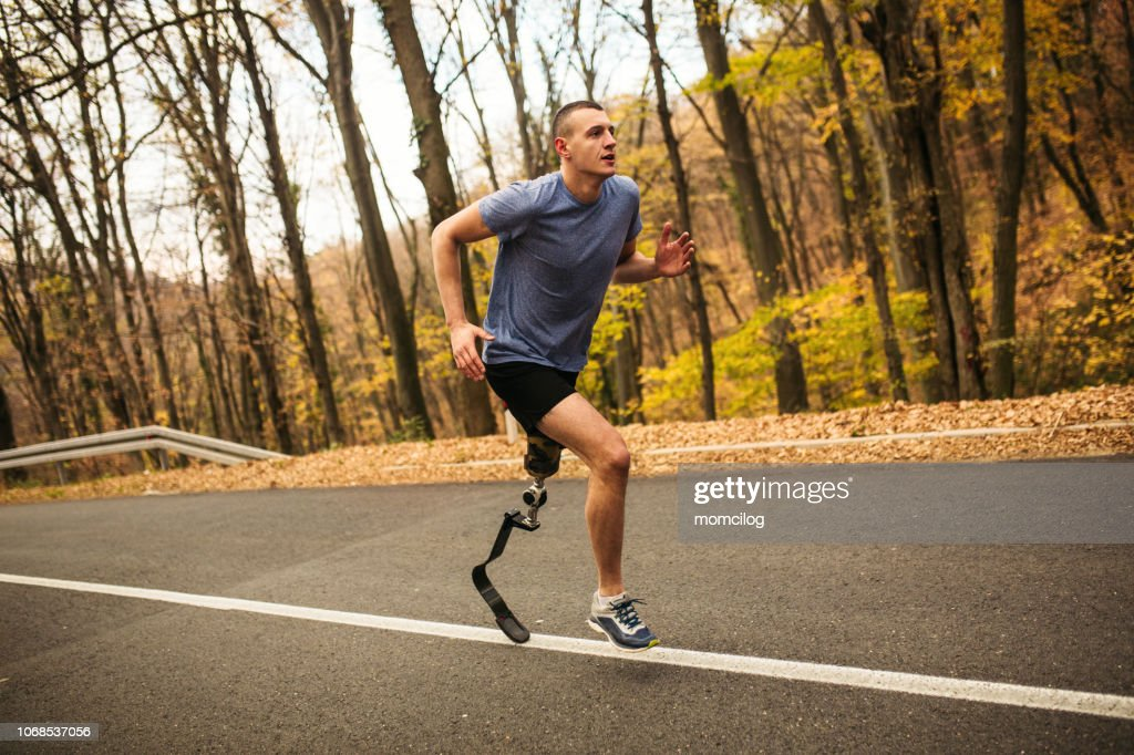 Young men with prosthetic legs running uphill in the forrest : Stock Photo