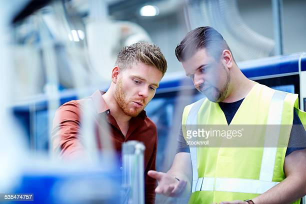 Young men working in manufacturing facility