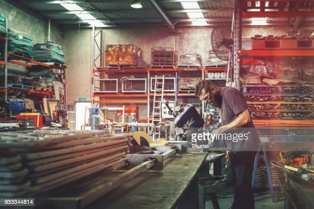 Young Metal Worker Using Power Tool In Factory With Protective Equipment